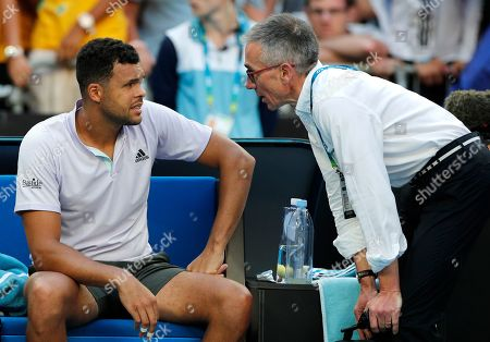 France's Jo-Wilfried Tsonga, left, talks with a tournament doctor before retiring from his first round match against Australia's Alexei Popyrin at the Australian Open tennis championship in Melbourne, Australia
