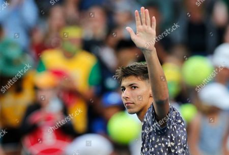 Australia's Alexei Popyrin waves to the crowd after France's Jo-Wilfried Tsonga retired injured from their first round singles match at the Australian Open tennis championship in Melbourne, Australia