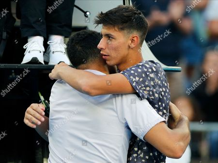 France's Jo-Wilfried Tsonga, left, is consoled by Australia's Alexei Popyrin after he retired injured from their first round singles match at the Australian Open tennis championship in Melbourne, Australia