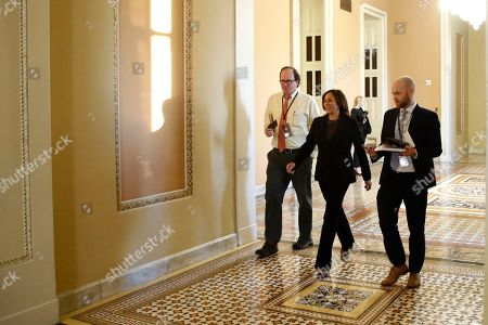 Sen. Kamala Harris, D-Calif., center, walks to the Senate chamber at the Capitol, in Washington. President Donald Trump's impeachment trial quickly burst into a partisan fight Tuesday as proceedings began unfolding at the Capitol