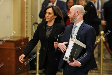 Sen. Kamala Harris, D-Calif, left, walks to the Senate chambers with an aide for the trial of President Donald Trump at the Capitol, in Washington