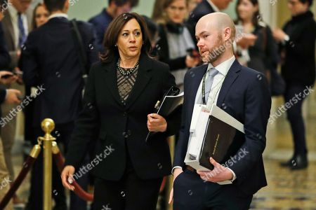Sen. Kamala Harris, D-Calif., left, walks to the Senate chamber with an aide at the Capitol, in Washington. President Donald Trump's impeachment trial quickly burst into a partisan fight Tuesday as proceedings began unfolding at the Capitol