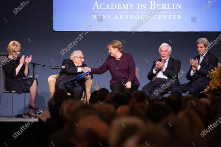 (L-R) American Academy Chairwoman Gahl Burt, former U.S State Secretary Henry Kissinger and German Chancellor Angela Merkel shaking hands, American Academy Trustee Gerhard Casper, Former United States Secretary of State John Kerry during the Henry Kissinger prize at the Great Orangery at Charlottenburg Palace in Berlin, Germany, 21 January 2020. The Henry Kissinger Prize is awarded by the American Academy in Berlin for exceptional contributions to transatlantic relations.