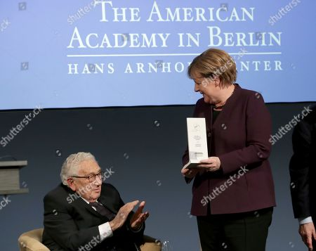 Stock Picture of Former US Secretary of State, Henry Kissinger, left, applaudes after German Chancellor Angela Merkel, right, received the 2020 Henry Kissinger Prize for her contribution to trans-Atlantic relations during a reception of the American Academy in Berlin, Germany