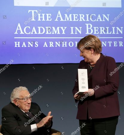 Former US Secretary of State, Henry Kissinger, left, applaudes after German Chancellor Angela Merkel, right, received the 2020 Henry Kissinger Prize for her contribution to trans-Atlantic relations during a reception of the American Academy in Berlin, Germany