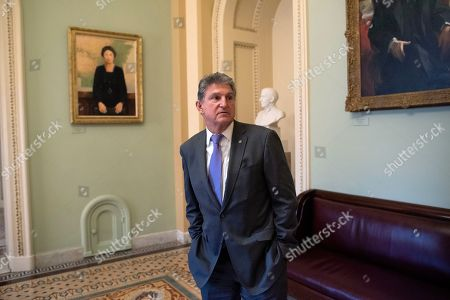 Sen. Joe Manchin, D-W.Va., pauses outside the Senate chamber at the Capitol in Washington,. President Donald Trump's impeachment trial quickly burst into a partisan fight Tuesday as proceedings began unfolding at the Capitol
