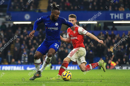Michy Batshuayi, Shkodran Mustafi. Chelsea's Michy Batshuayi controls the bll by Arsenal's Shkodran Mustafi during the English Premier League soccer match between Chelsea and Arsenal at Stamford Bridge stadium in London England
