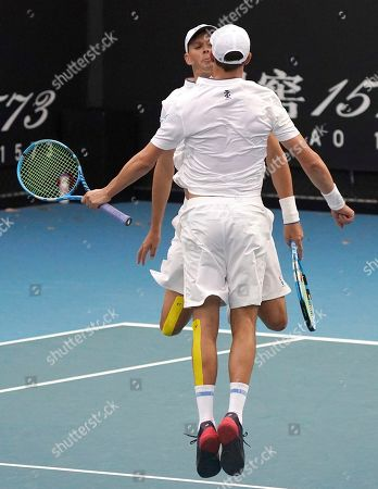 Bob, left, and Mike Bryan of the U.S.celebrate their their first round doubles win over India's Rohan Bopanna and Japan's Yasutaka Uchiyama at the Australian Open tennis championship in Melbourne, Australia