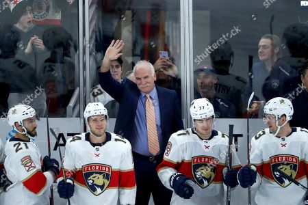 Florida Panthers head coach and former Chicago Blackhawks coach, Joel Quenneville acknowledges the crowds applause during the first period of an NHL hockey game between the Blackhawks and Panthers, marking Quenneville's return as a head coach, in Chicago