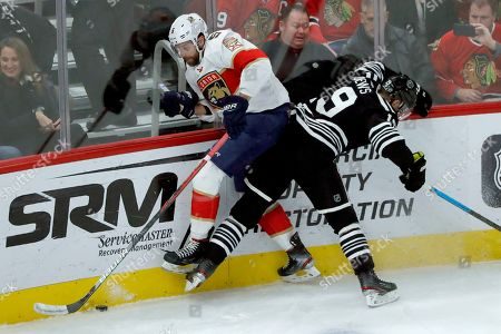 Aaron Ekblad, Jonathan Toews. Chicago Blackhawks' Jonathan Toews (19) checks Florida Panthers' Aaron Ekblad against the boards during the first period of an NHL hockey game, in Chicago