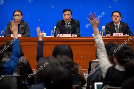 Li Bin, center, deputy director of China's National Health Commission, waits as journalists raise their hands to ask questions during a press conference about a new type of coronavirus spreading in China at the State Council Information Office in Beijing, . The number of cases of a new virus has risen to 440 in China and all the deaths had been in Hubei province, home to Wuhan city where the first illnesses from coronavirus were reported in late December