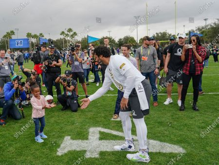 Seattle Seahawks Quarterback Russell Wilson plays ball with his daughter Sienna  as his wife Ciara (right) takes pictures.