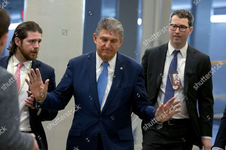Sen. Joe Manchin, D-W.Va., walks past reporters on his way to the Senate chamber, on Capitol Hill in Washington, for the impeachment trial if President Donald Trump