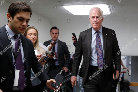Stock Image of Senate Majority Whip Sen. John Cornyn, R-Texas, right, is followed by reporters as he walks to attend the impeachment trial of President Donald Trump on charges of abuse of power and obstruction of Congress, on Capitol Hill in Washington