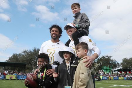 NFC quarterback Russell Wilson, left, of the Seattle Seahawks with son Future Zahir Wilburn, and NFC quarterback Drew Brees of the New Orleans Saints with sons Bowen Christopher Brees, Baylen Robert Brees, and Callen Christian Brees pose for a photo after Pro Bowl NFL football practice, in Kissimmee, Fla