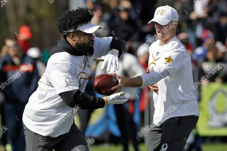 Ezekiel Elliott, Drew Brees. NFC running back Ezekiel Elliott (21), of the Dallas Cowboys, takes a handoff from quarterback Drew Brees (9), of the New Orleans Saints, during a practice for the NFL Pro Bowl football game, in Kissimmee, Fla