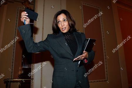 Stock Photo of Sen. Kamala Harris, D-Calif., talks to reporters while leaving the Senate chamber during a break the impeachment trial of President Donald Trump at the Capitol in Washington