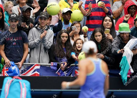 Ashleigh Barty of Australia signs autographs for spectators after winning her first round doubles match with Julia Goerges of Germany against Astra Sharma of Australia and Jessica Moore of Australia on day four of the Australian Open tennis tournament at Melbourne Park in Melbourne, Australia, 23 January 2020.
