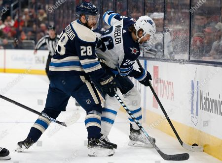 Columbus Blue Jackets' Oliver Bjorkstrand, left, of Denmark, tries to steal the puck from Winnipeg Jets' Blake Wheeler during the third period of an NHL hockey game, in Columbus, Ohio. The Blue Jackets defeated the Jets 4-3
