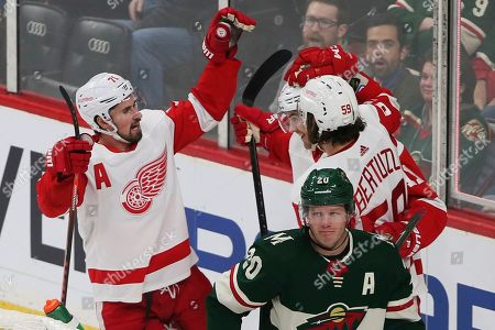 Filip Zadina, Ryan suter. Detroit Red Wings' Filip Zadina, second from right, top, of Czech Republic is congratulated by teammates on his first of two goals off Minnesota Wild's Devan Dubnyk in the first period of an NHL hockey game, in St. Paul, Minn. Skating away, foreground, is Minnesota Wild's Ryan Suter