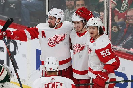 Detroit Red Wings' Filip Zadina, center, of Czech Republic is congratulated by teammates on his first of two goals off Minnesota Wild's Devan Dubnyk in the first period of an NHL hockey game, in St. Paul, Minn
