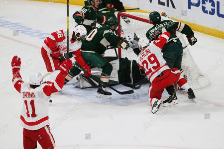 Detroit Red Wings' Filip Zadina, lower left, of Czech Republic, celebrates his power play goal off Minnesota Wild's Devan Dubnyk in the first period of an NHL hockey game, in St. Paul, Minn. It was Zadina's second goal of the period