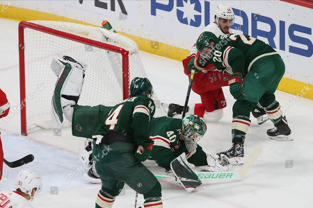 Devan Dubnyk, Ryan Suter, Robby Fabbri. Minnesota Wild's Devan Dubnyk dives to smother the puck as Ryan Super, right, keeps Detroit Red Wings' Robby Fabbri in check in the first period of an NHL hockey game, in St. Paul, Minn. The Wild won 4-2