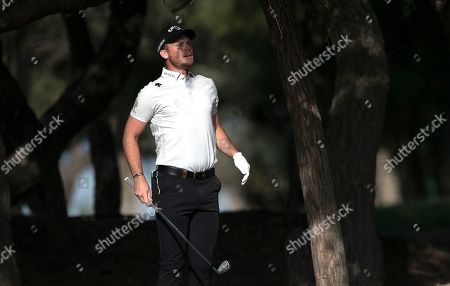 England's Danny Willett jumps up on the 13th hole during the first round of the Dubai Desert Classic golf tournament in Dubai, United Arab Emirates