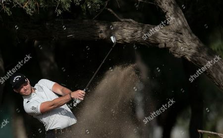 England's Danny Willett plays a shot on the 13th dirt during the first round of the Dubai Desert Classic golf tournament in Dubai, United Arab Emirates