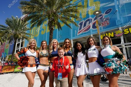 Stock Photo of AFC Cheerleaders, (from left to right) Samantha Reynolds of the Cincinnati Bengals, Taylor B of the Jacksonville Jaguars, Elizabeth Franklin of the Tennessee Titans, Melissa of the Los Angeles Chargers, Ambria of the Indianapolis Colts, Jenna of the New York Jets and Paige B of the Miami Dolphins, pose for a group photo with Braydon Bent