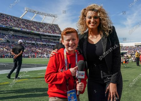 Braydon Bent of NFL UK poses for a photo with national anthem singer Tori Kelly
