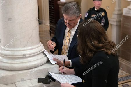 Sen. Joe Manchin, D-W.Va., looks over paperwork with a staffer near the Senate chamber during the impeachment trial of President Donald Trump at the Capitol, in Washington