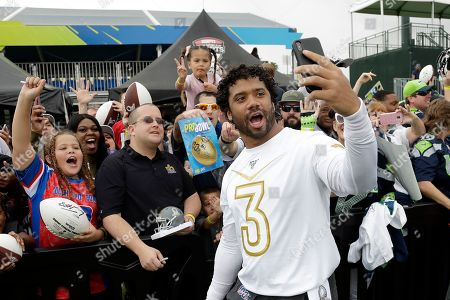 NFC quarterback Russell Wilson, of the Seattle Seahawks, live videos fans after a practice for the NFL Pro Bowl football game, in Kissimmee, Fla
