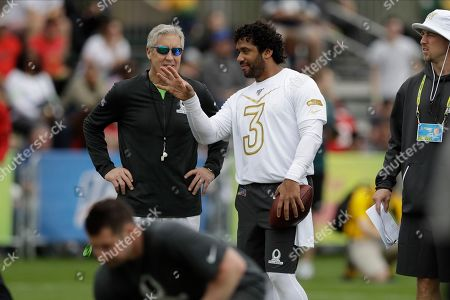 NFC quarterback Russell Wilson, of the Seattle Seahawks, (3) talks to head coach Pete Carroll, also of the Seattle Seahawks, during a practice for the NFL Pro Bowl football game, in Kissimmee, Fla