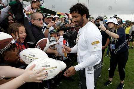 NFC quarterback Russell Wilson, of the Seattle Seahawks, signs autographs for fans after a practice for the NFL Pro Bowl football game, in Kissimmee, Fla