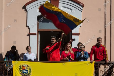 President of Venezuela, Nicolas Maduro (L), waves a Venezuelan national flag along with his wife Cilia Flores (R) during an event at the end of a march through the streets of Caracas, Venezuela, 23 January 2020. Venezuela commemorates 62 years of the fall of the dictatorship of Marcos Perez Jimenez, amid the political dispute between the leadership of the ruling party and the opposition that do not recognize each other. The Chavista government organized an 'anti-imperialist march' in western Caracas with which it hopes to reach the Miraflores Palace, the seat of the Executive. It is, according to the ruling leaders, a demonstration 'against treason against the people', in reference to the democratic governments that settled in Venezuela from 1958 until the so-called Bolivarian revolution came to power in 1999.