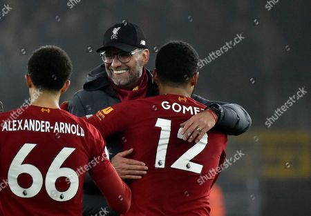 Liverpool's manager Jurgen Klopp, center, celebrates with Liverpool's Trent Alexander-Arnold, left, and Liverpool's Joe Gomez at the end of the English Premier League soccer match between Wolverhampton Wanderers and Liverpool at the Molineux Stadium in Wolverhampton, England