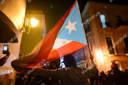 Protesters hold a Puerto Rican flag during a protest in San Juan, Puerto Rico, . Hundreds of people joined a protest Thursday organized by Puerto Rican singer Rene Perez of Calle 13 fame in a demonstration reminiscent of those that ousted the island's former governor last year. Anger is growing over emergency aid that until recently sat unused in a warehouse amid ongoing earthquakes