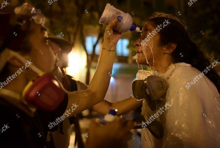 Ana Maria Abruna, photojournalist, receives a dose of solution after being exposed to tear gas during a protest in San Juan, Puerto Rico, . Hundreds of people joined a protest Thursday organized by Puerto Rican singer Rene Perez of Calle 13 fame in a demonstration reminiscent of those that ousted the island's former governor last year. Anger is growing over emergency aid that until recently sat unused in a warehouse amid ongoing earthquakes