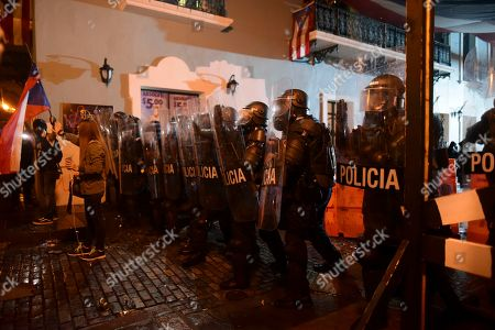 Policemen stand guard during a protest in San Juan, Puerto Rico, . Hundreds of people joined a protest Thursday organized by Puerto Rican singer Rene Perez of Calle 13 fame in a demonstration reminiscent of those that ousted the island's former governor last year. Anger is growing over emergency aid that until recently sat unused in a warehouse amid ongoing earthquakes