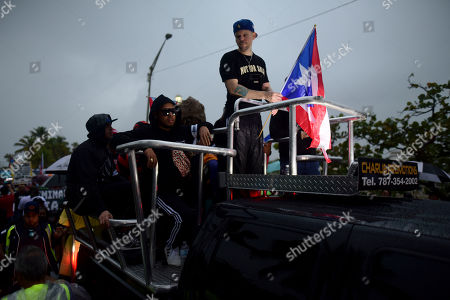 Puerto Rican singer Rene Perez of Calle 13 leads a protest over emergency aid that until recently sat unused in a warehouse amid ongoing earthquakes, in San Juan, Puerto Rico