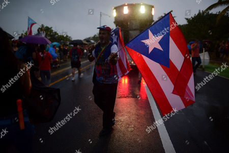 A man sells Puerto Rican flags under the rain during a protest organized by Puerto Rican singer Rene Perez of Calle 13 over emergency aid that until recently sat unused in a warehouse amid ongoing earthquakes, in San Juan, Puerto Rico, . Protesters demanded the ouster of Gov. Wanda Vazquez