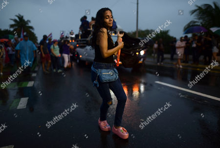 A woman dances under the rain during a protest organized by Puerto Rican singer Rene Perez of Calle 13 over emergency aid that until recently sat unused in a warehouse amid ongoing earthquakes, in San Juan, Puerto Rico, . Protesters demanded the ouster of Gov. Wanda Vazquez