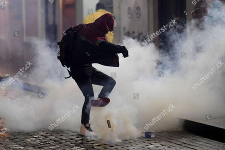 A demonstrator kicks a gas canister during a protest over emergency aid, in San Juan, Puerto Rico, . Hundreds of people joined a protest Thursday organized by Puerto Rican singer Rene Perez of Calle 13 fame in a demonstration reminiscent of those that ousted the island's former governor last year. Anger is growing over emergency aid that until recently sat unused in a warehouse amid ongoing earthquakes