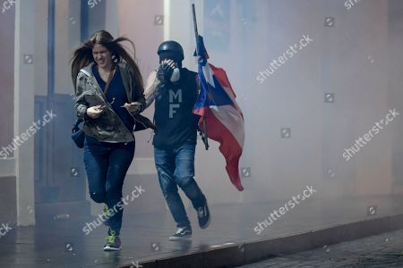 Demonstrator run away from a gas cloud during a protest over emergency aid, in San Juan, Puerto Rico, . Hundreds of people joined a protest Thursday organized by Puerto Rican singer Rene Perez of Calle 13 fame in a demonstration reminiscent of those that ousted the island's former governor last year. Anger is growing over emergency aid that until recently sat unused in a warehouse amid ongoing earthquakes