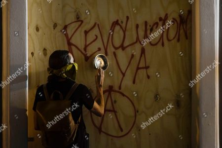 "A protester hits a wooden panel with a casserole during a protest in San Juan, Puerto Rico, . Hundreds of people joined a protest Thursday organized by Puerto Rican singer Rene Perez of Calle 13 fame in a demonstration reminiscent of those that ousted the island's former governor last year. Anger is growing over emergency aid that until recently sat unused in a warehouse amid ongoing earthquakes. The slogan reads ""revolution now"