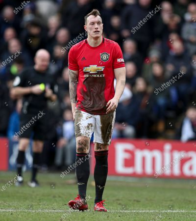 Phil Jones of Manchester United is covered in mud