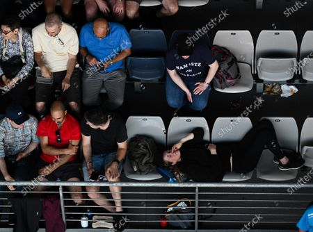 A women resting on seats in the Melbourne Arena during the Men's Singles Third Round match between Ernests Gulbis and Gael Monfils