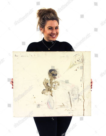 Auctioneer Briony Harford with the self portrait by Pete Doherty of himself and Kate Moss drawn using his own blood