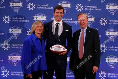 New York Giants NFL football quarterback Eli Manning poses with owners Laurie Tisch, left, and John Mara, right, after announcing his retirement, in East Rutherford, N.J